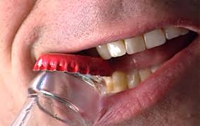 opening a bottle with teeth