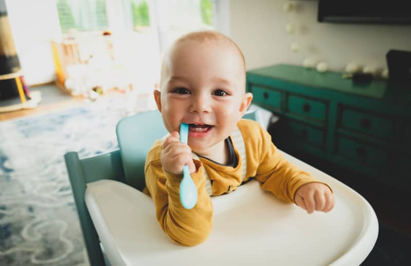 toddler in feeding chair with spoon in mouth smiling