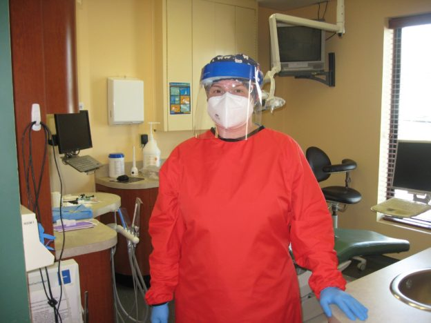 dental hygienist in pandemic protective clothing